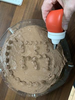 Das Frostig des gesunden Kuchens für den Geburtstag dekorieren