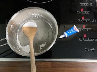 Isomalt mit blauer Lebensmittelfarbe im Topf erhitzen