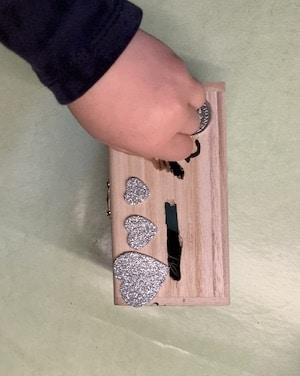 Spar-Holzschatulle mit Münzen füllen